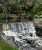 Water flowing over historic stone weir