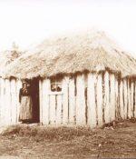 Old Woman standing in door of old wooden slub hut